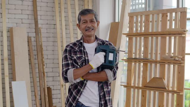 vidéos et rushes de entrepreneuriat de portrait de charpentier aîné âgé 61 ans regardant l'appareil-photo et souriant tout en étant dans une bonne humeur. grand-père mûr aîné heureux avec le sourire toothy à la maison. soins de santé pour personnes âgées. conce - new age concept