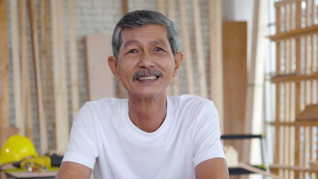 vidéos et rushes de portrait de l'esprit d'entreprise des hommes menuisiers âgés de 61 ans regardant l'appareil-photo et souriant tout en étant de bonne humeur. grand-père mûr aîné heureux avec le sourire toothy à la maison. soins de santé pour personnes âgée - new age concept