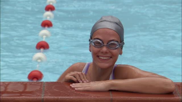 vídeos y material grabado en eventos de stock de portrait female swimmer swimming up to side of pool / resting - gorro de baño