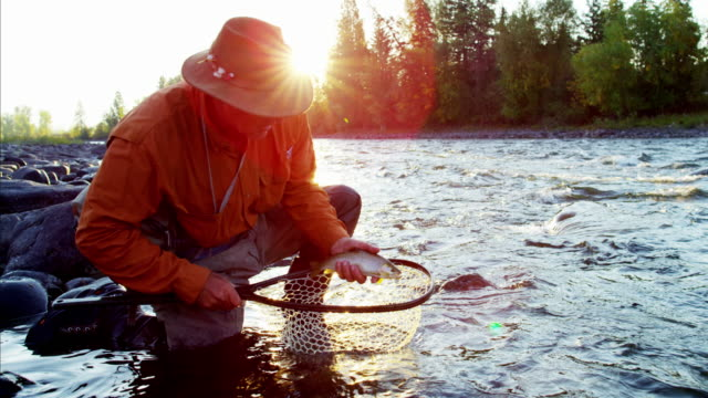 Portrait fisherman with fish in keep net Canada