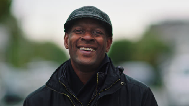 SLO MO. Portrait. Focus racks to African American man in winter coat and hat laughs at camera as he stands in empty neighborhood street on overcast day.
