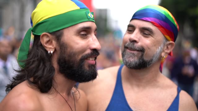 vídeos de stock, filmes e b-roll de casal de gays de retrato comemorando na parada gay - 40 49 anos