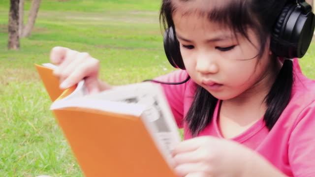 porträt-mädchen-lesebuch und hören von musik im kopfhörer im park. - kindertag stock-videos und b-roll-filmmaterial
