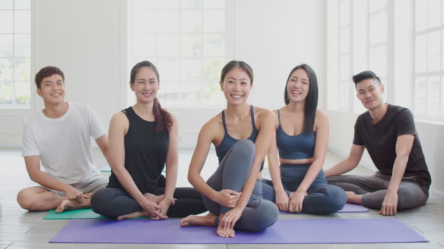 vídeos de stock, filmes e b-roll de grupo retrato de pessoas asiáticas sorrindo relaxando e olhando para a câmera na aula de yoga - zen
