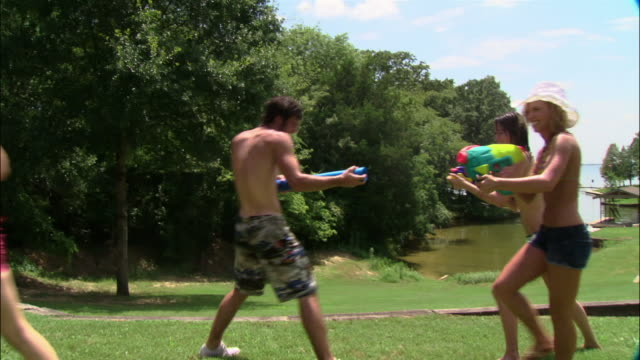 MS portrait group of young men and women having water gun fight on lawn/ Texas
