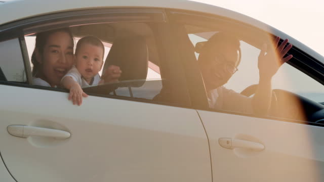 portrait happy asian family with babyboy looking out car windows.active parents and people outdoor activity on summer vacations with baby.happy family holidays.family,lifestyle,people,life insurance,parenthood concept.vacations - istock - young family stock videos & royalty-free footage