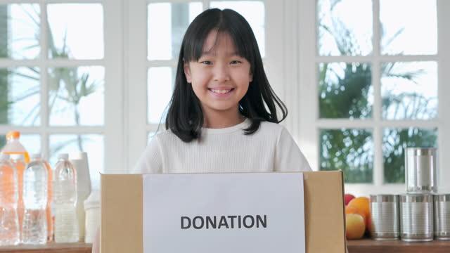 ritratto felice ragazza asiatica di 9 anni in possesso di piccola scatola invitano a donare qualcosa e guardando la telecamera per la videochiamata a casa. insegnare ai bambini il concetto di sostenibilità. - altruismo video stock e b–roll