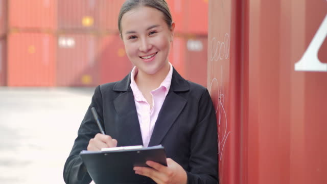portrait happy asian women engineer looking at camera and check loading containers box from cargo freight.delivery,commerce,growth,connection,business,empowerment,leadership,women in stem,industry and transportation concept.cargo containers - chinese ethnicity stock videos & royalty-free footage