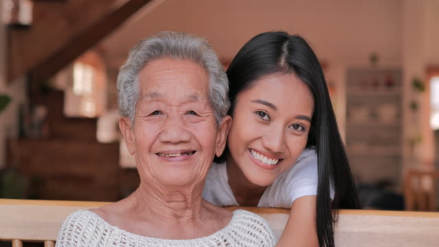 portrait happy volunteer young black woman nurse caretaker talking with asian senior grandmother patient laughing bonding looking at camera in home.medical,healthcare,caretaking,care,retirement,family,lifestyle,volunteer,charity,nursing home concept. - korean ethnicity stock videos & royalty-free footage