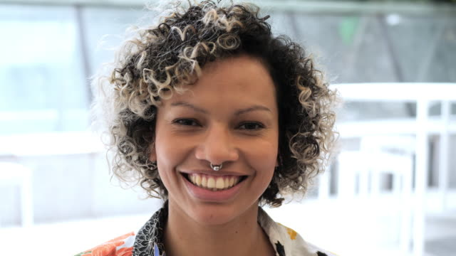 portrait headshot of colombian woman with curly hair - piercing video stock e b–roll