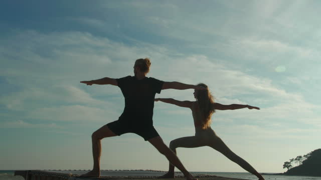 portrait, in silhouette of couples young adult age 25-29 yearold practicing yoga in outdoors on a summer while mountain background with reflection sunlight together.they are performing yoga on sunlight shine day.sport prep concept. - slim stock videos & royalty-free footage