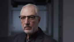 Portrait Intelligent CEO Mature Man in Eyeglasses. Face Successful Middle Aged Man Thinking and Stand Alone. Pensive Elegant 60s Person Looking at Camera Closeup. Confident Professional Older Engineer