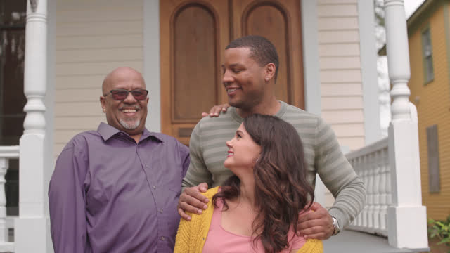 portrait. new homeowner laughs with his wife and father-in-law in front of their new house - three people stock videos & royalty-free footage