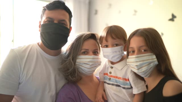 portrait o family using face mask at home - family with two children stock videos & royalty-free footage
