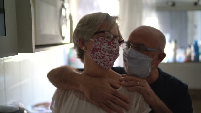portrait o senior couple using face mask at home - safety stock videos & royalty-free footage