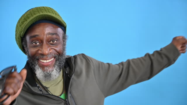 portrait of 57 year old black man smiling and dancing - coloured background stock videos & royalty-free footage