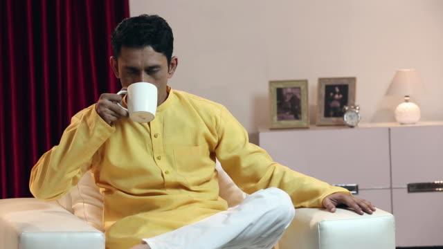 stockvideo's en b-roll-footage met portrait of a adult man drinking tea, delhi, india - driekwartlengte