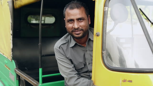 vidéos et rushes de portrait of a auto rickshaw driver smiling, delhi, india - indien d'inde