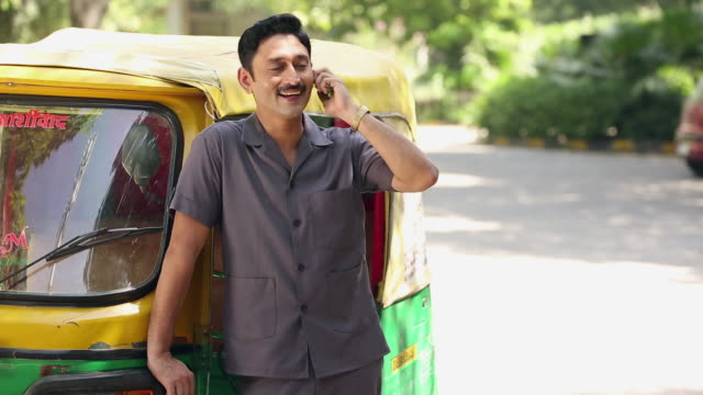 portrait of a auto rickshaw driver talking on a mobile phone, delhi, india  - 人力車点の映像素材/bロール