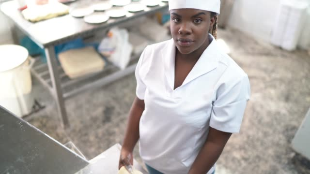 portrait of a baker in a commercial kitchen preparing dough - production line stock videos & royalty-free footage