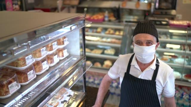 stockvideo's en b-roll-footage met portret van een bakkerijwerknemer die brood in een kleinhandelsvertoning met gezichtsmasker schikt - bakkerij
