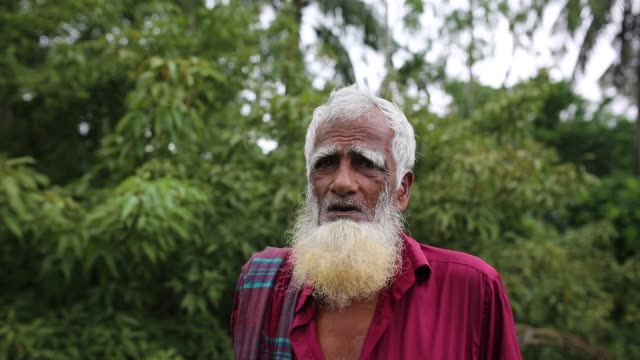 vídeos y material grabado en eventos de stock de portrait of a bangladeshi old man near in dhaka , bangladesh on july 27, 2018. almost three-quarters of the population live in rural areas. families... - posa del loto