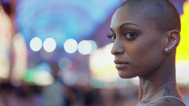 slo mo. cu. portrait of a beautiful african-american woman standing on fremont st. in las vegas - millionnaire stock videos & royalty-free footage