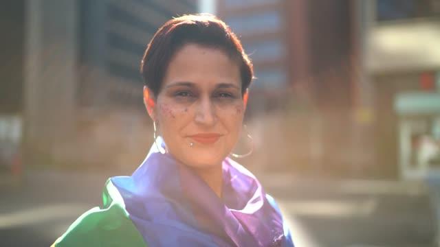 vídeos de stock, filmes e b-roll de retrato de uma mulher bonita e confiável que usa a bandeira do arco-íris durante a parada de lgbtqi - flag
