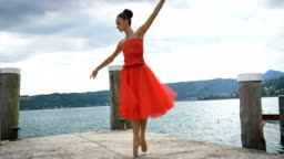 Portrait of a beautiful light ballerina, in a lush red dress, while she is dancing.
