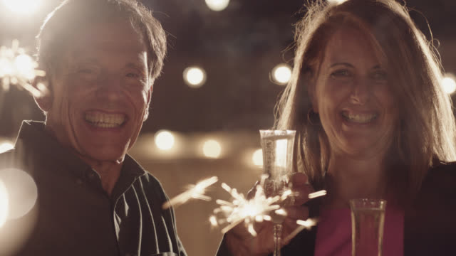 vídeos y material grabado en eventos de stock de slo mo. portrait of a beautiful middle aged couple toasting champagne and holding sparklers - 50 54 años