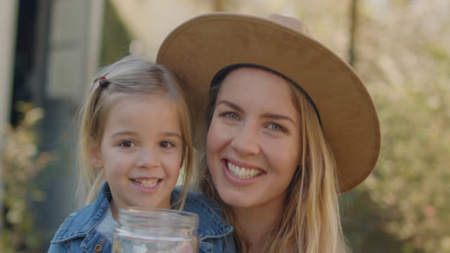slo mo cu portrait of a beautiful mother and daughter holding a jar of trash outside - collection stock videos & royalty-free footage