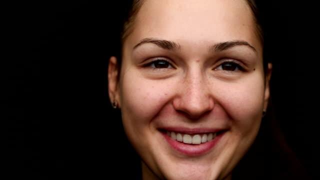 portrait de la jolie jeune fille sur fond noir, gros plan. beau sourire
