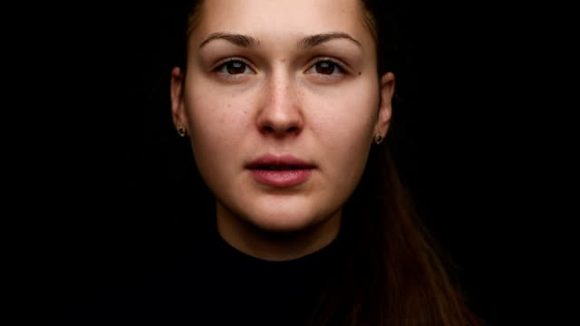 portrait of a beautiful young girl on a black background. close-up. Dolly