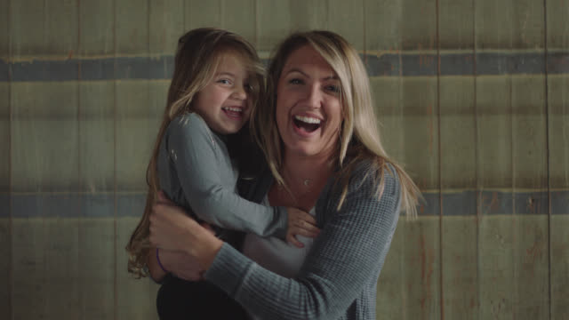 portrait of a beautiful young woman and her daughter smiling at the camera - capelli biondi video stock e b–roll