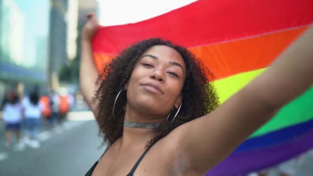 portrait of a beautiful young woman holding rainbow flag during lgbtqi parade - pride stock videos & royalty-free footage
