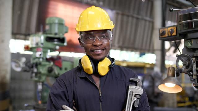 stockvideo's en b-roll-footage met portret van een zwarte afrikaanse mens in een fabriek - hoofddeksel