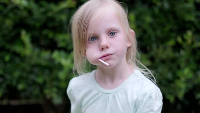 ロリポップを食べる金髪の女の子の肖像画 - 人間の舌点の映像素材/bロール