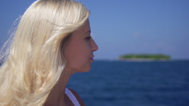 portrait of a blonde woman looking at a tropical island from the beach. - slow motion - goodsportvideo stock videos and b-roll footage