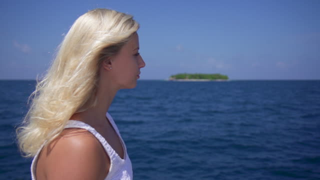 Portrait of a blonde woman looking at a tropical island from the beach. - Slow Motion