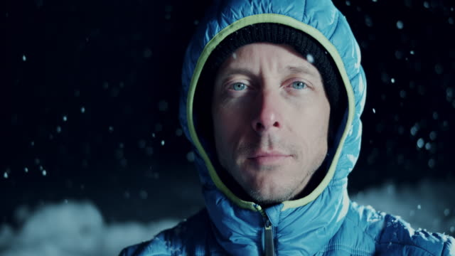 slo mo portrait of a blue eyed man in snowfall - ski jacket stock videos & royalty-free footage