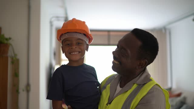 portrait of a boy at home wearing helmet in the arms of his grandfather - after work stock videos & royalty-free footage