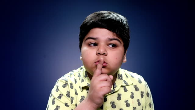Portrait of a boy doing silence gesture
