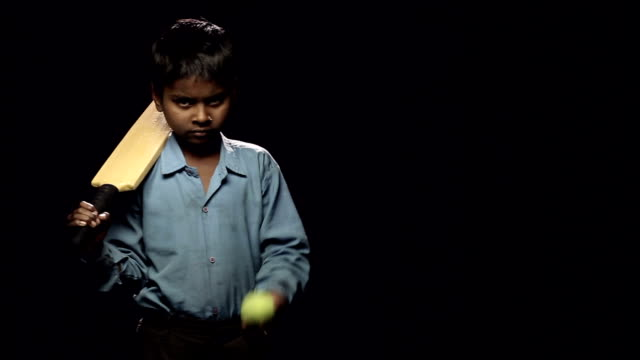 vídeos de stock, filmes e b-roll de portrait of a boy holding cricket bat and ball - balançando