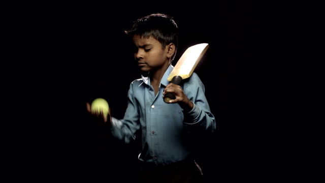 Portrait of a boy holding cricket bat and ball