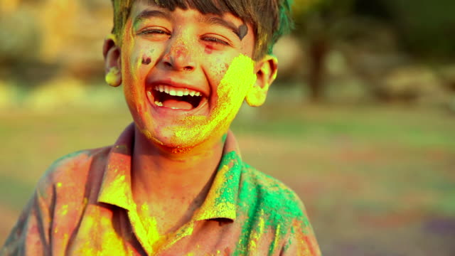 vídeos y material grabado en eventos de stock de portrait of a boy playing holi and laughing, delhi, india - holi