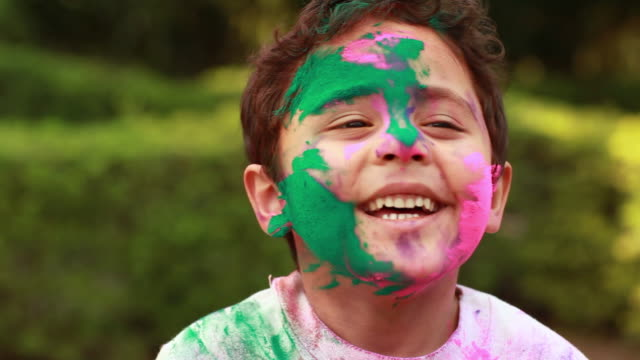 vídeos de stock, filmes e b-roll de portrait of a boy playing holi and laughing, delhi, india - meninos
