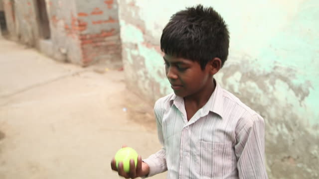 portrait of a boy playing with cricket ball, faridabad, haryana, india  - cricket ball stock videos & royalty-free footage