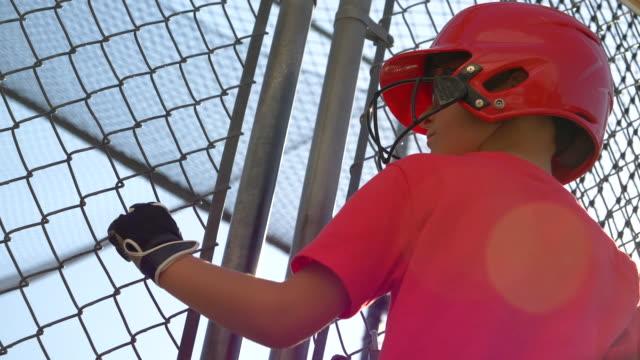 a portrait of a boy practicing little league baseball at the batting cages. - slow motion - gabbia di battuta video stock e b–roll