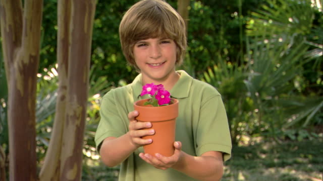 Portrait of a boy presenting a potted flower to the viewer.