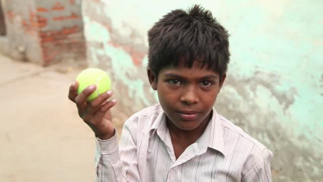 portrait of a boy showing cricket ball, faridabad, haryana, india  - slum stock videos & royalty-free footage